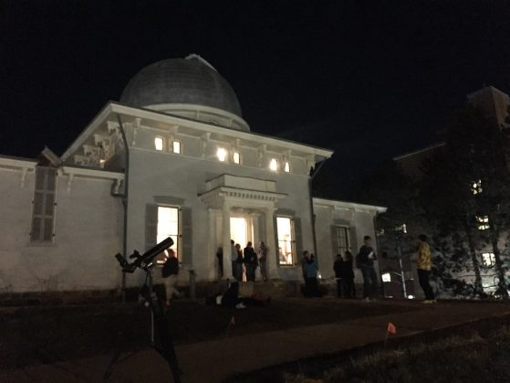 Visitors on the observatory lawn, with a telescope and light pollution demonstration.