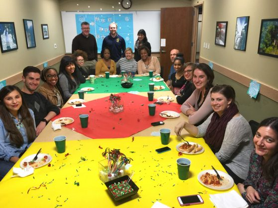 CGIS staff and students gathered around a decorated table enjoying the holidays spirit