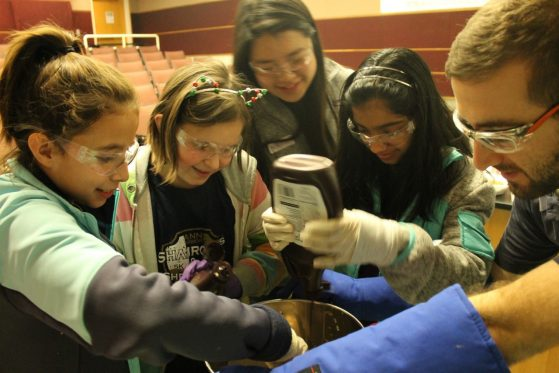 girl putting chocolate syrup in a bowl where liquid nitrogen is steaming off while a group of girls watches with graduate student