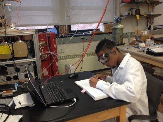 Black student in safety glasses and lab coat at work at a table in a lab