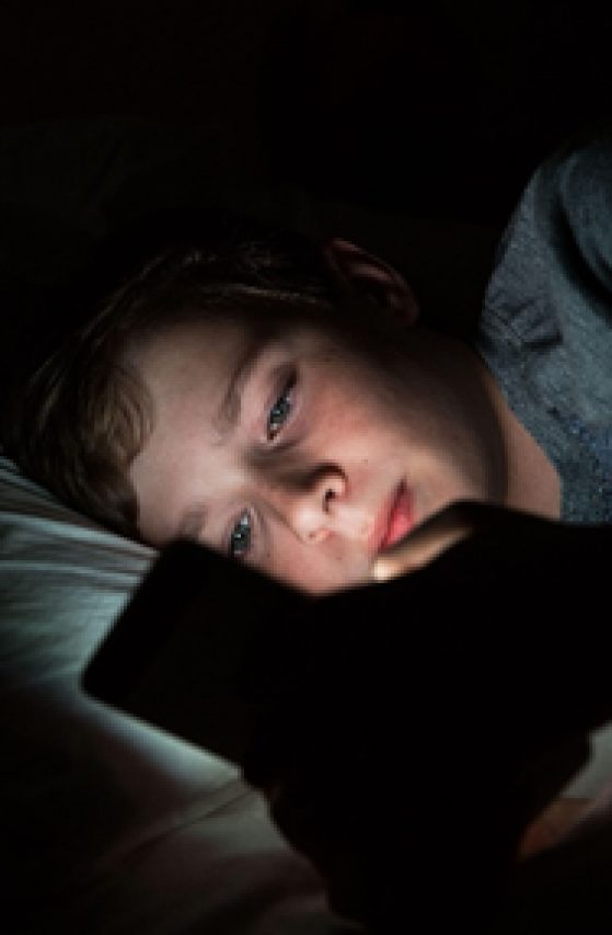 Child in bed, looking at phone.