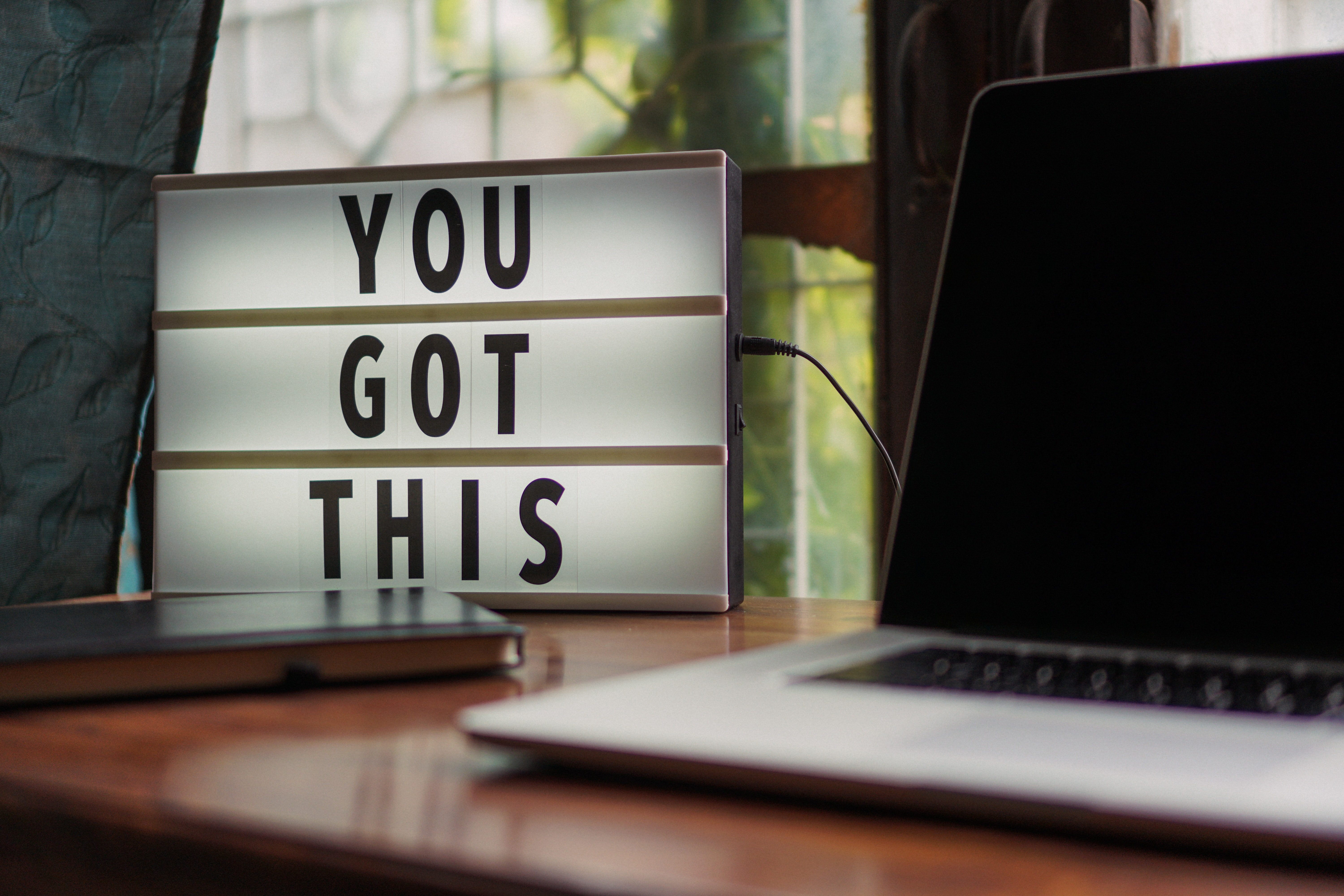 "A sign saying ""You Got This"" next to a laptop"