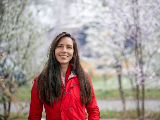 Giorgia Auteri in a red jacket standing in front of trees blurred in the background. Image: Isa Betancourt