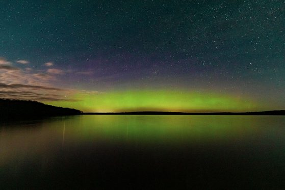 """Spring aurora borealis on Douglas Lake,"" University of Michigan Biological Station, Pellston, Michigan. The sky is green, purple, pink and orange over the lake with land visible on the far shore."