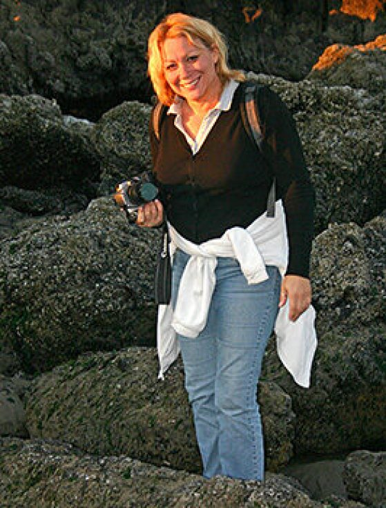Linda Garcia standing on large boulders with her camera