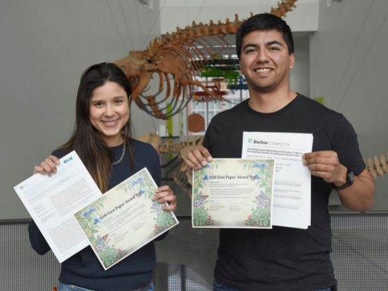 Sara Colom and Peter Cerda hold up their certificates and copies of their papers in the musem atrium with prehistoric whales in the background