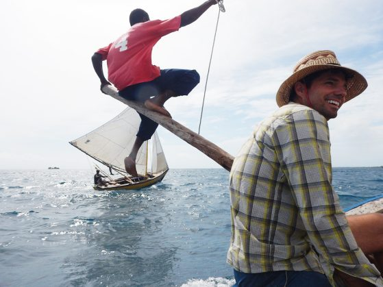 Jacob Allgeier headed to a field site in Haiti to build artificial reefs. He's on a boat with another researcher and another sailboat is in view