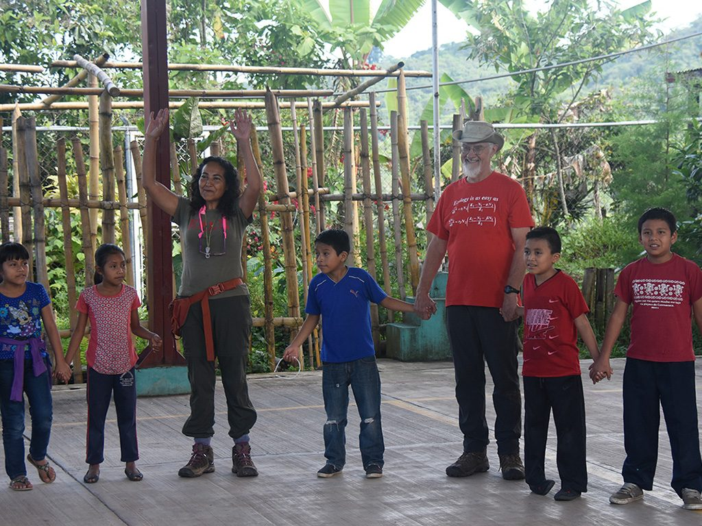 Ivette Perfecto (arms raised) and John Vandermeer play an ecological game with the children during Ecodía.