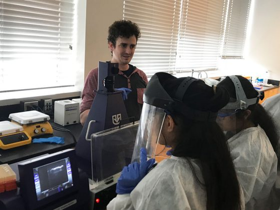Kevin Amses stands facing two students who are wearing face visors and standing at a computer.