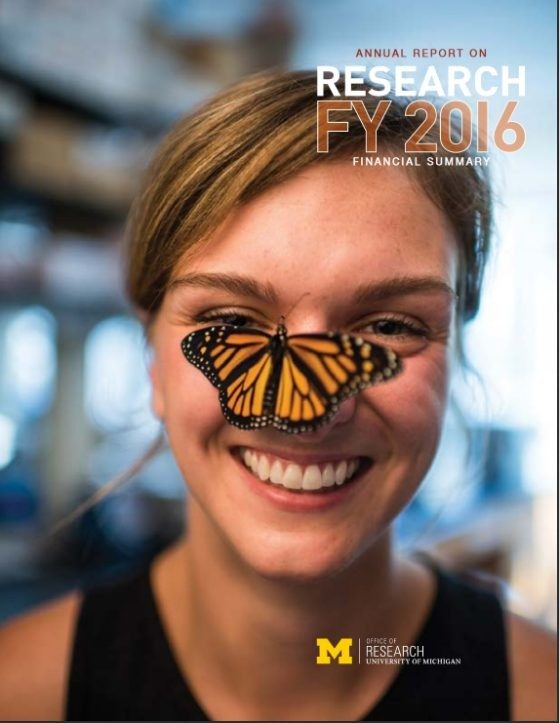Smiling young woman with a monarch butterfly perched on the woman's nose