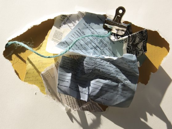Several fragments of crumpled paper resting in a larger paper fragment. There is a binder clip and a strand of yarn. The writing is not legible.