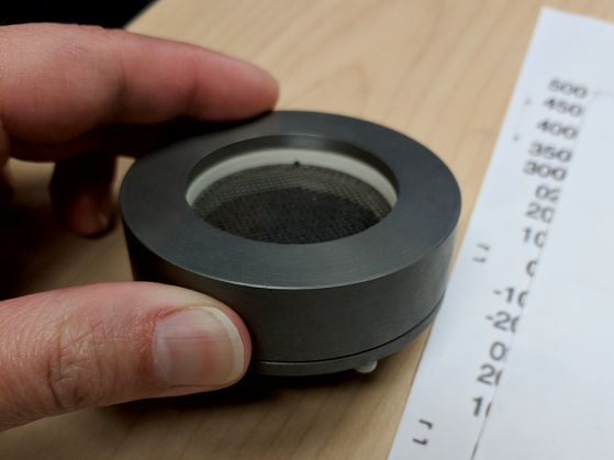 A photograph of an early prototype of the Faraday cup. It's a black round piece that appears hollow in the center. It is positioned between an index finger and a thumb on a table.