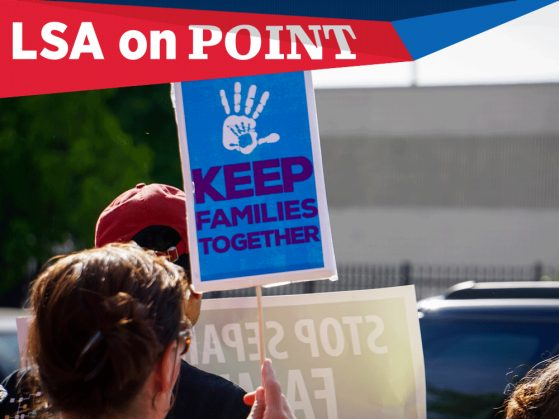 A photograph of a a sign that says Keep families together beneath a child's hand print. The photograph also has a text flag that says LSA on Point.