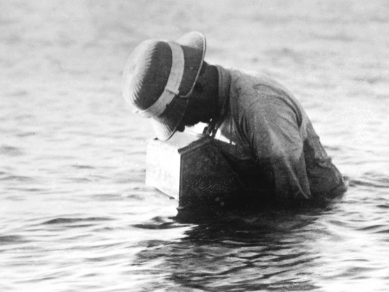 A black-and-white photograph of Reighard standing in waist-deep water taking photographs within the watertight box he had designed.