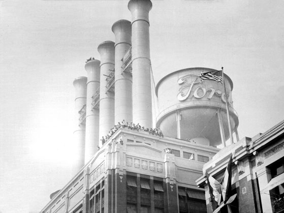 Detail view of the smokestacks and water tower of the power plant at Ford Motor Company Highland Park designed by architect, Albert Kahn, with men standing along top corner of building and one of the smokestacks.