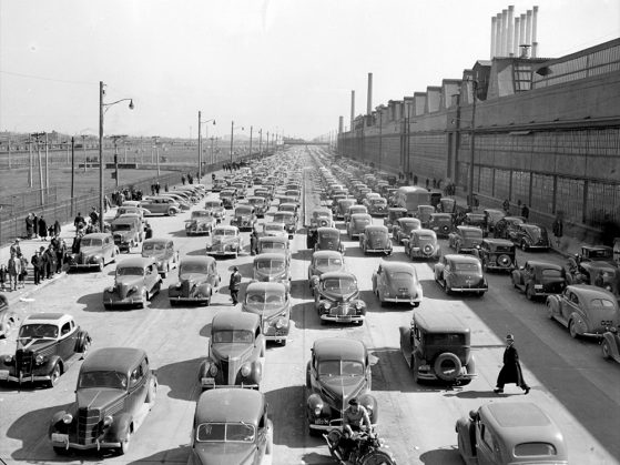 A black-and-white photograph of several very long lines of cars outside the River Rouge plant. The street is adjacent to the plant, which towers above it. Seven slender smokestacks reach up from its roof to the sky. The photo is taken from above, and you can see a few people walking beside and between cars.