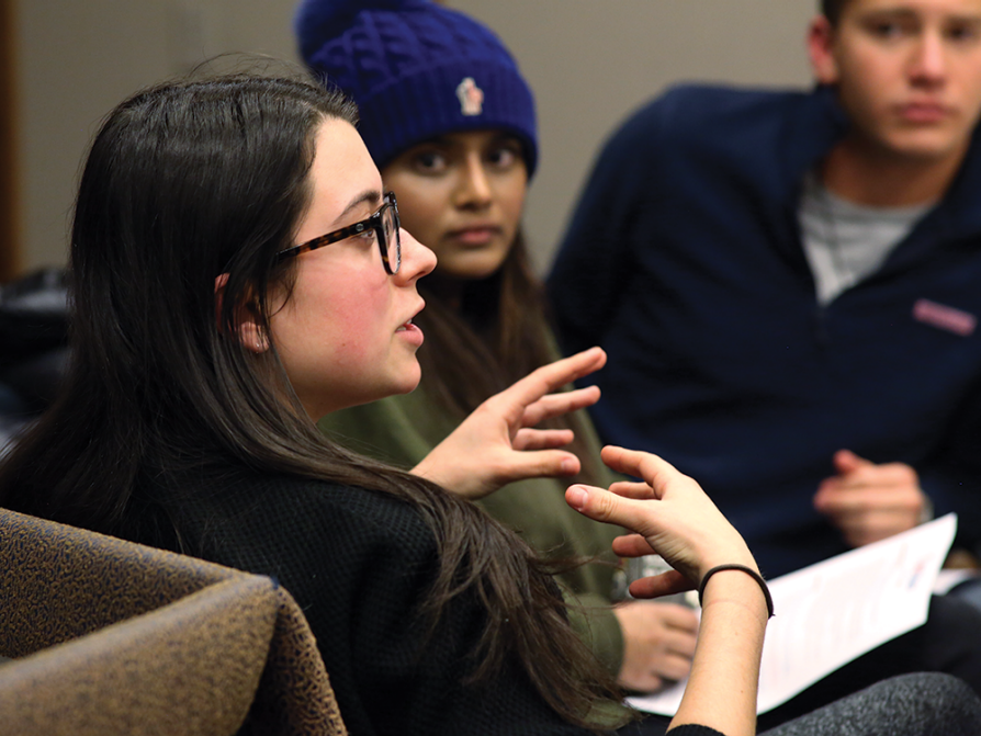A woman is talking and gesturing with her hands. Other students are looking intently at her.