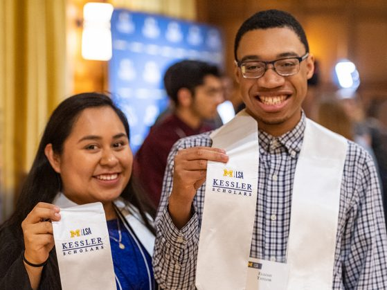 Erica Gonzalez-Paramo and Elijah Taylor smile at the camera. They are each wearing a graduation stole, and they each lift the right side for the camera, which says M|LSA Kessler Scholars