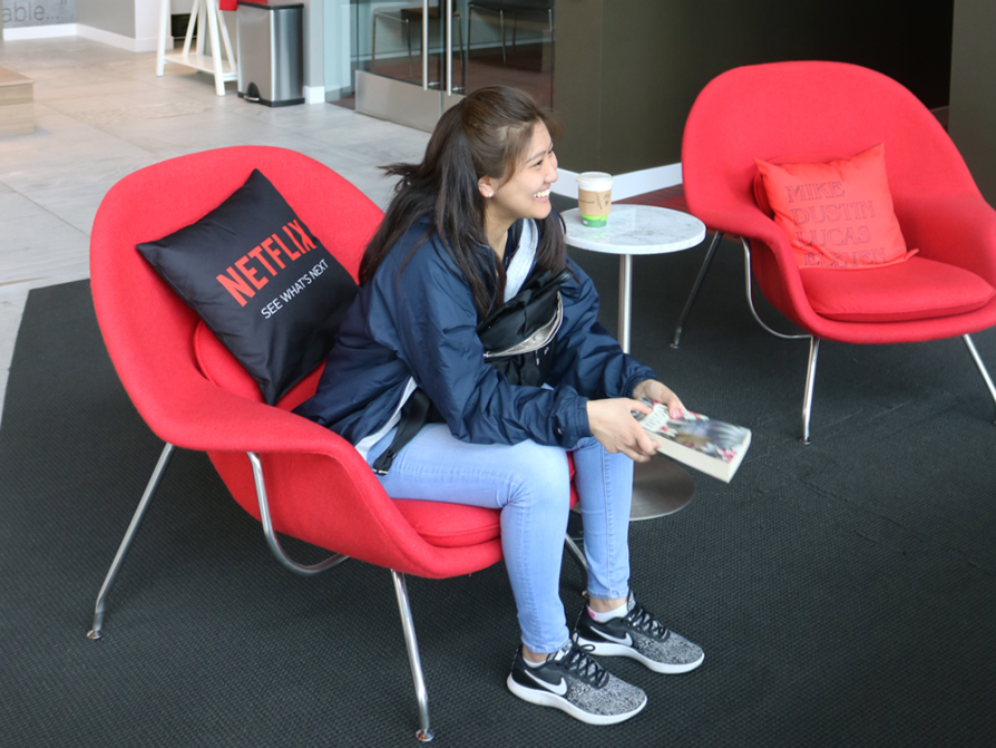 A beaming student who is sitting on a bright red chair. A black throw pillow behind her says Netflix.