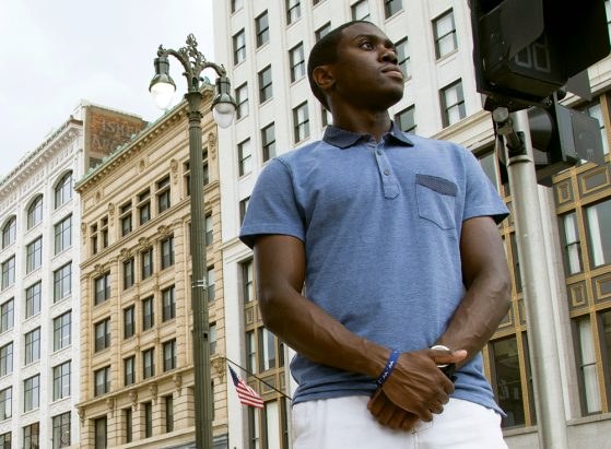 A photograph of a young man wearing a light blue short-sleeved shirt. He's standing on a city street, near a crosswalk.