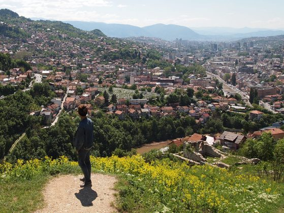 "Hunter Zhao standing atop a hill and looking down at the Bijela Tabija (""White Castle:) historical district in Sarajevo, a town nestled into a valley. Mountains are visible in the distance."