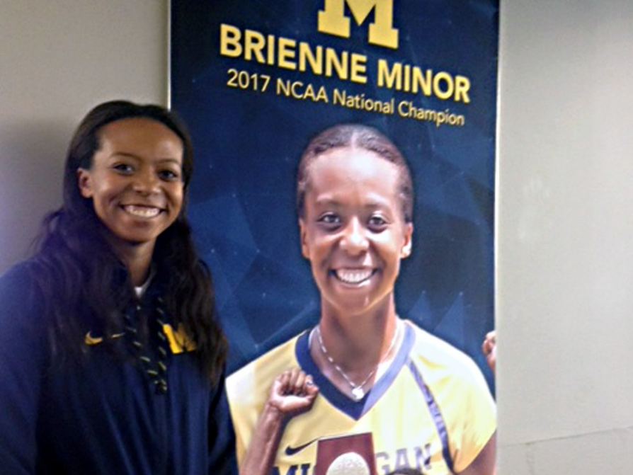 Brienne Minor standing next to the U-M tennis banner that bears her photograph.