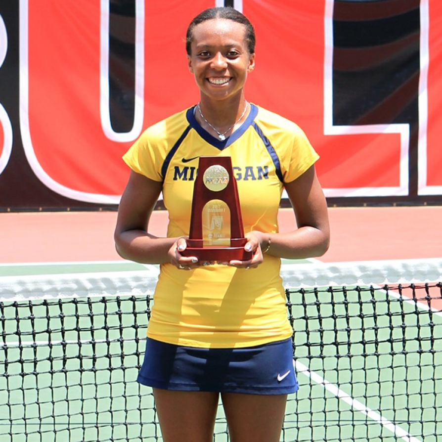 Brienne Minor stands in front of the net on a tennis court wearing her gold U-M tennis team uniform. She is holding a trophy .