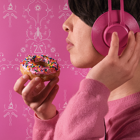 Figure with pink headphones on, holding a donut with pink frosting and sprinkles.