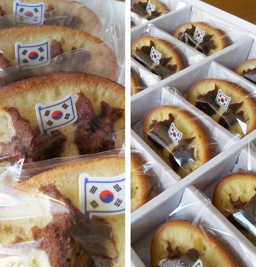 Dokdo bread in packaging tray. On the individual pieces of bread, the dark outline of the islands is visible against the lighter part. A Korean flag is planted in the brad islands.