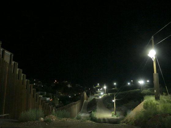 A photograph of the border at night. The dark sky is punctuated by a series of distant streetlights,and fainter lights can be seen of a city below the road. The fence rises and dips along with the road.