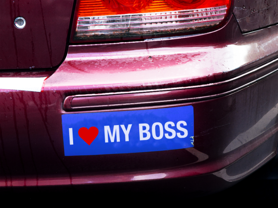 A photograph of a car bumper with a bumper sticker that says I heart my boss.