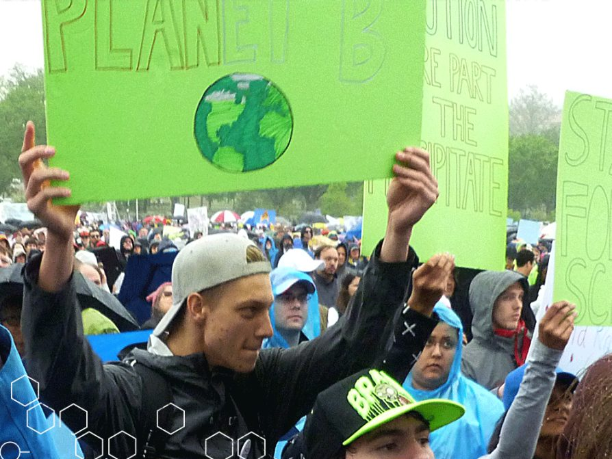 Man standing in the crowd at the Science March holding up a green sign that says Planet B