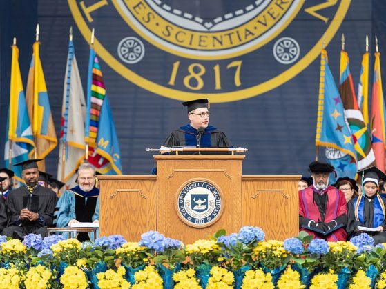 Dean Andrew Martin, in full commencement regalia, stands at the lectern to address the 2018 graduating class.