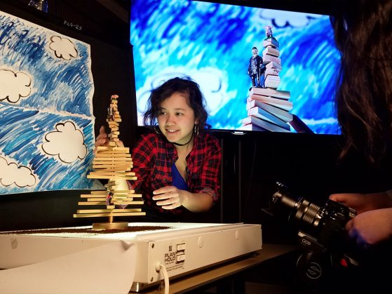 A student stacking a tall, complicated stack of blocks. There is a simple drawing of white puffy clouds in a blue sky. A projection on a screen shows the clouds in the sky and it also mirrors the student stacking blocks.