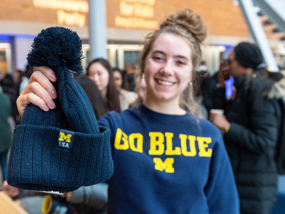 Student wearing U-M sweatshirt and holding an M | LSA winter hat