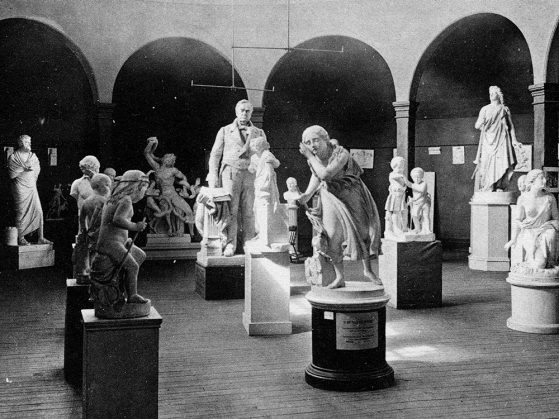 A black and white photograph of a collection of sculptures in a room with arches and mottled light.