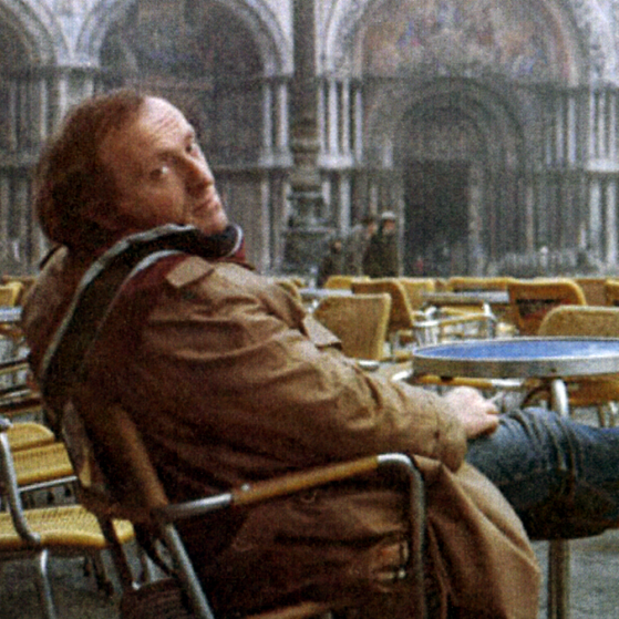 Joseph Brodsky sitting in an empty outdoor cafe looking back over his right shoulder.