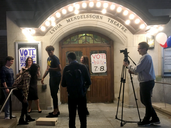 Students filming a PSA outside of Lydia Mendelssohn Theatre. Five students stand outside the building, which has a poster on its door that says VOTE *here* 7am-8pm and another on its announcement board. Another student stands behind a camera filming them. Three helium balloons are tied to the railing: one red, one white, one blue.