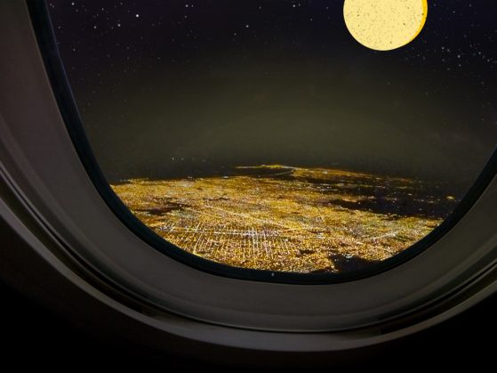 A nighttime view of an illuminated city from an airplane window.