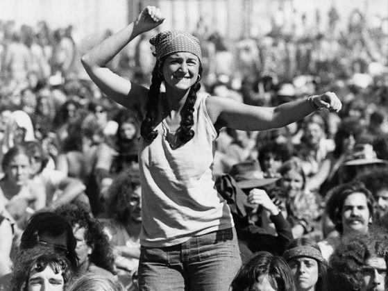 Black and white photo of woman in a crowd on someone's shoulders with her fist in the air.