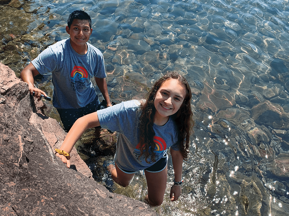 Two students stand near a rock in shallow water looking up