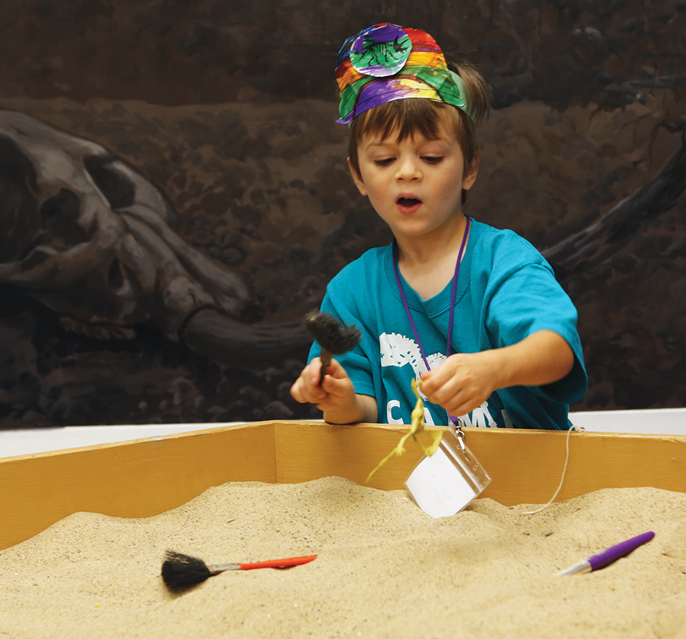 A small child looks for fossils in sand.