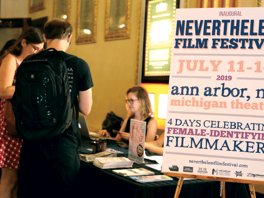 A photograph of people standing at the table in front of a table at the Nevertheless Film Festival.