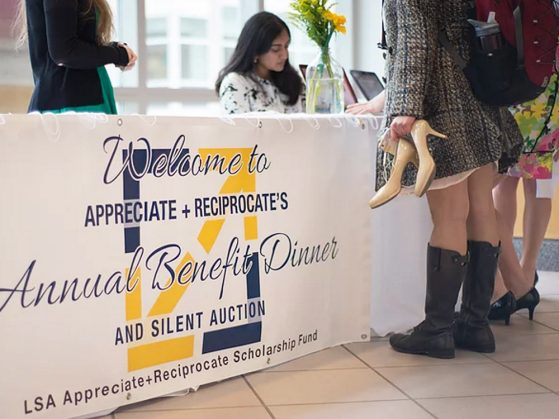 A table with a banner for the Appreciate-Reciprocate scholarship dinner. One student sits behind the table, and two women stand in front of it seen from the waist down. One of the women is carrying pumps and wearing winter boots.