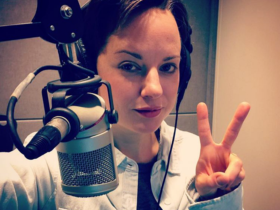 Jones-Rooy stands behind a broadcasting microphone holding the index and middle fingers up as a peace sign. She's wearing headphones.