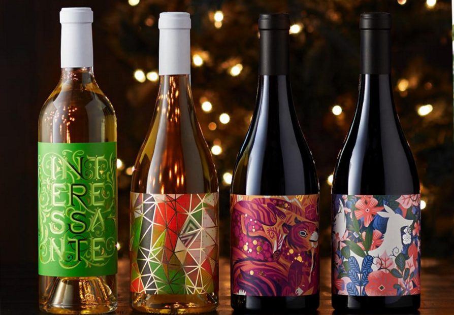 Four wine bottles with a background of small white lights. The two bottles on the left are white wines. The two on the right are red wines. All of the labels have patterns of bright, vibrant colors.