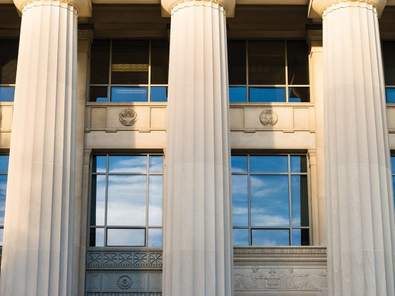 A photograph of the pillars of Angell Hall in which the windows reflect a bright blue sky and streaks of clouds.