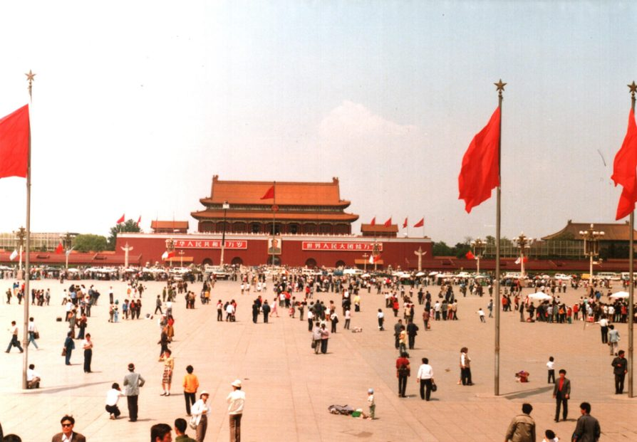 A photograph of Tiananmen Square taken in 1988. There are three red flags in the foreground and small groups of people standing or talking together in the square.