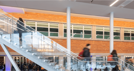 Interior view of the new LSA Building addition with students ascending and descending the central staircase.