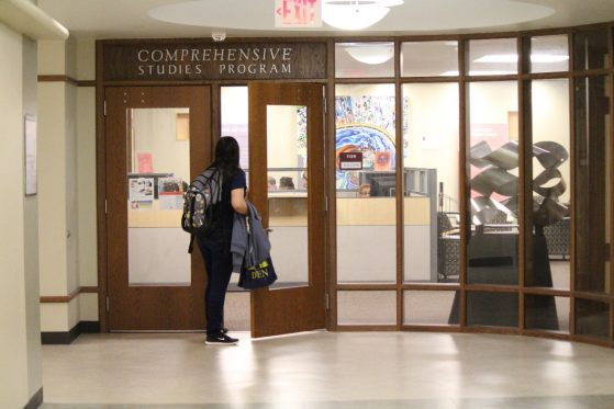 A student is pictured walking through the double doors of CSP's on-campus office, pre-COVID.